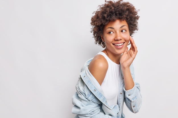 Studio shot of happy woman keeps hand on face looks back with glad carefree expression notices something pleasant away shows bare shoulder wears denim long sleeved shirt isolated on white wall