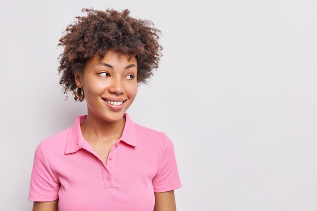 Studio shot of happy woman with curly hair feels glad smiles pleasantly dressed in casual pink t shirt isolated over white wall