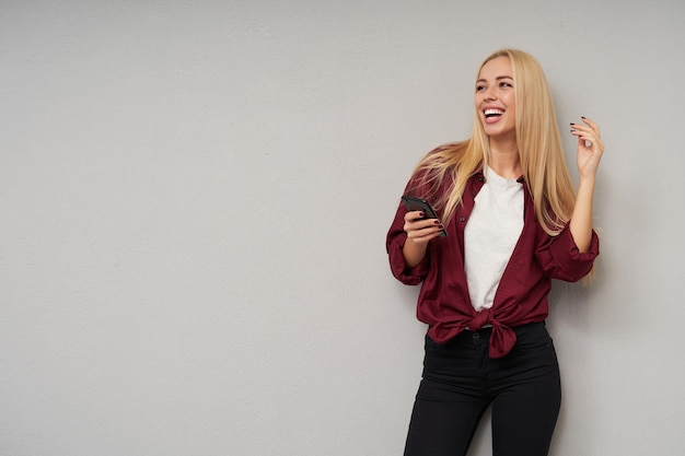 Studio shot of happy young blonde female with loose hair laughing happily while looking aside, dressed in burgundy shirt and white t-shirt while posing over light grey background