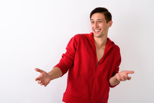 Studio shot of happy young handsome man smiling while looking co