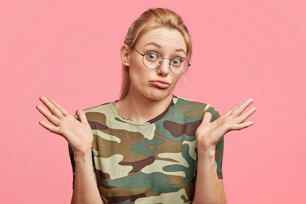 Studio shot di esitante giovane femmina bionda con espressione incerta, scrolla le spalle, si sente esitazione riguardo a prendere una decisione, isolato su rosa