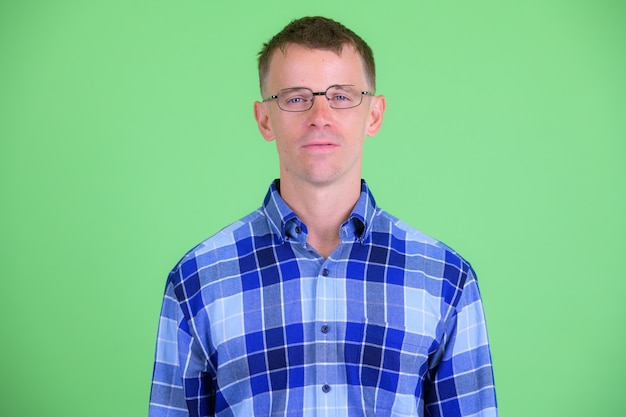 Studio shot of hipster man wearing eyeglasses against green background