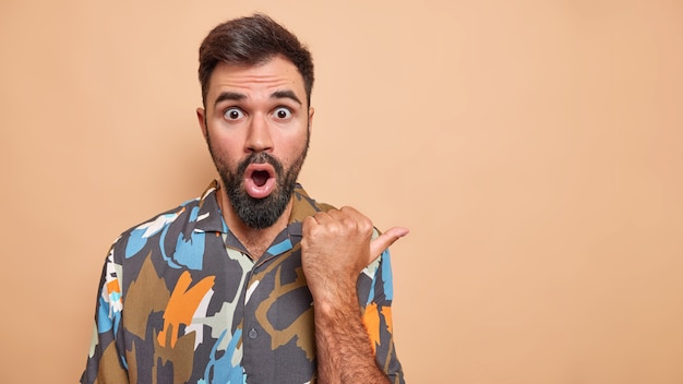 Studio shot of impressed bearded man opens mouth and points away being shocked