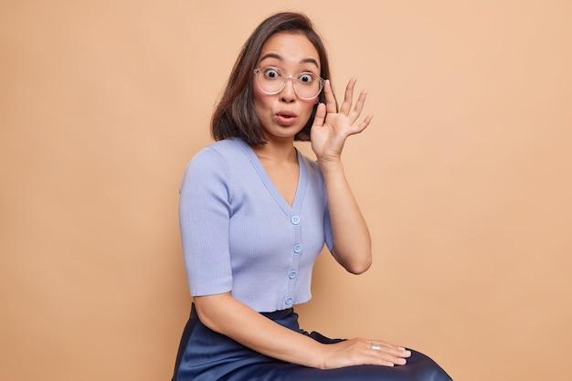 Foto in studio di una giovane donna asiatica impressionata con i capelli scuri che fissa impressionata