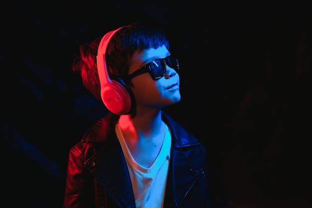ネオンライトのある暗いスタジオで撮影されたスタジオ。ヘッドフォンでスタイリッシュな男の子の肖像画