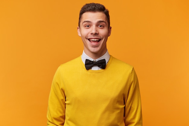 Studio shot of joyful sociable young attractive guy, smartly dressed in a yellow sweater with bow-tie