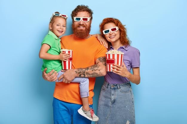 Studio shot di adorabili coppie dai capelli rossi hanno un fine settimana, andare al cinema per guardare il nuovo film, indossare occhiali stereo, mangiare fast food