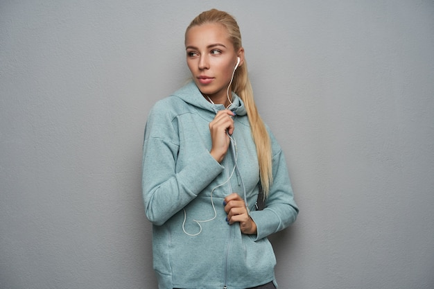 Studio shot of lovely young sporty blonde woman with ponytail hairstyle listening to music with headphones and looking aside with serious face, dressed in athletic wear over light grey background