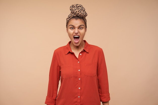 Studio shot of mad young pretty brunette woman shouting angrily while looking at front, keeping her hands along body while standing over beige wall