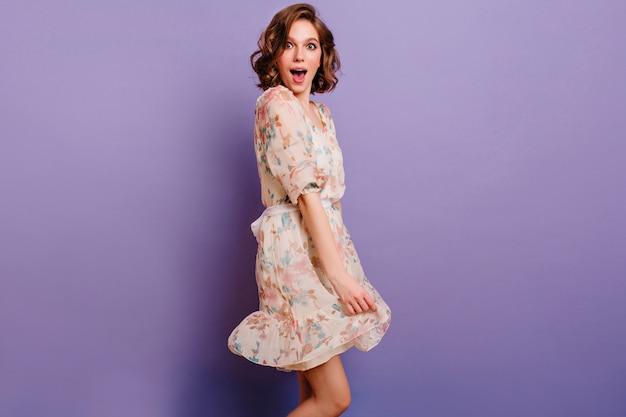 Studio shot di magnifica giovane donna con capelli castano scuro gioca con il vestito
