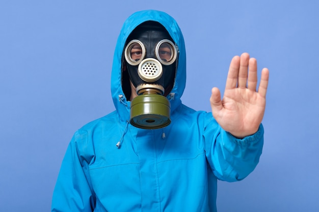 Studio shot of man dresses chemical protective suit and respirator posing and showing stop gesture
