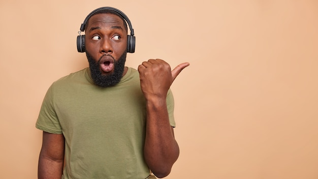 Studio shot of man with thick beard points thumb away on blank space listens music via wireless headphones dressed in casual t shirt isolated over beige wall