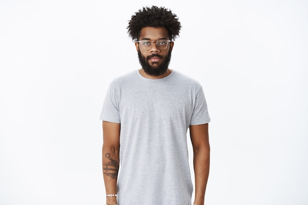 Studio shot of masuline african american male with curly hair and beard wearing nose earring and glasses looking at front with calm casual expression in ordinary pose over gray wall