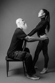 Studio shot of mature bearded bald man and young beautiful asian woman together against gray wall in black and white