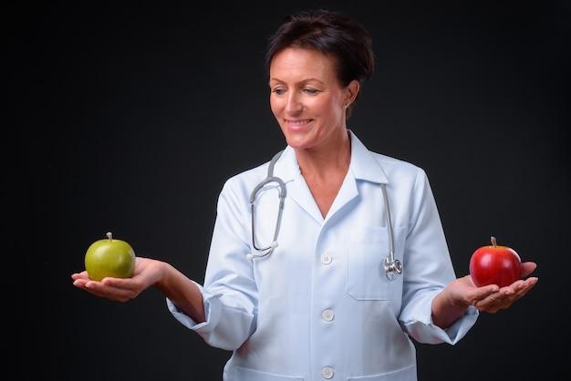 Studio shot of mature beautiful scandinavian woman doctor with short hair against black background