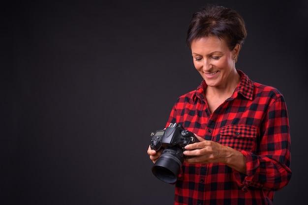 Studio shot of mature beautiful scandinavian woman with short hair against black background