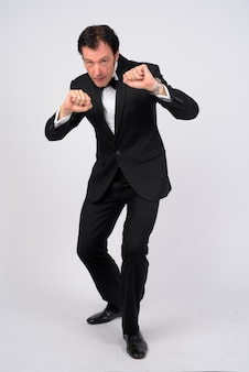 Studio shot of mature handsome businessman wearing tuxedo against white