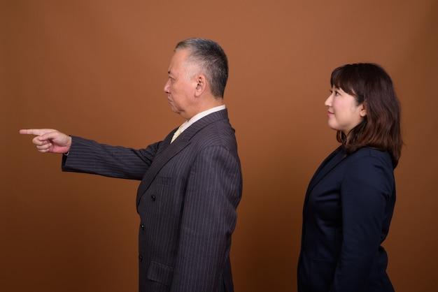 Studio shot of mature japanese businessman and mature japanese businesswoman together against brown background