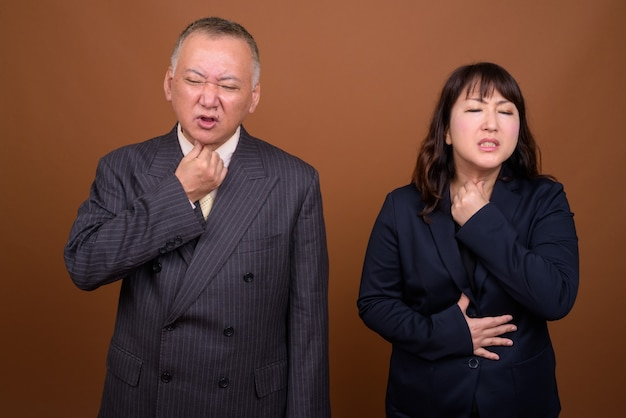 Studio shot of mature japanese businessman and mature japanese businesswoman together against brown background
