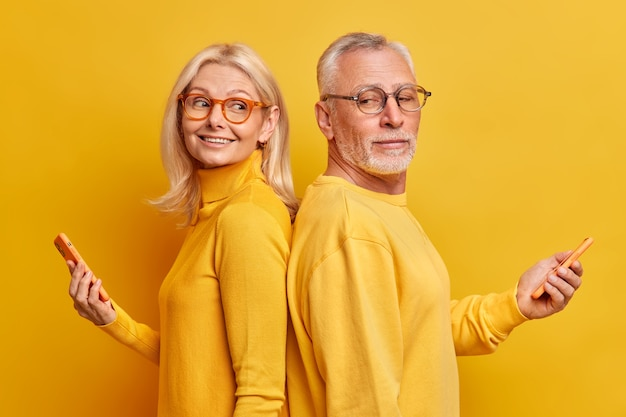Studio shot of mature male and female models stand back to each other with modern gadgets in hands surf internet chat in social networks isolated over yellow wall