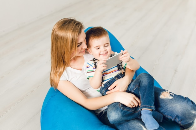 Studio shot of a mother holding her child in arms. boy plays on smartphone and smiles