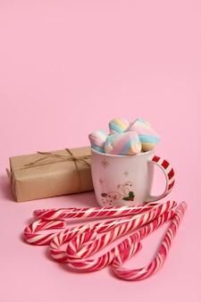 Studio shot of mug with colorful marshmallows, christmas gift in craft wrapping paper and striped candy canes on pink colored background. christmas and new year concept with copy space for ad