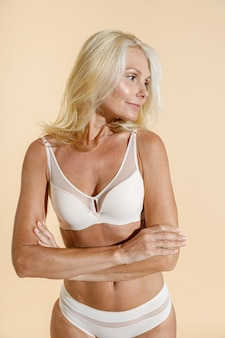 Studio shot of natural caucasian mature woman looking away while standing isolated over beige