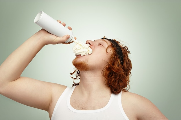 Studio shot of obese overweight caucasian man with ginger curly hair, spraying whipped cream in his mouth