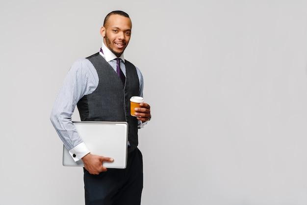 ノートパソコンと行くコーヒーを保持しているアフリカ系アメリカ人のビジネスマンのスタジオ撮影。