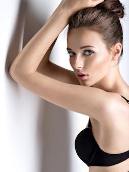 검은 브래지어를 입고 긴 머리를 가진 아름답고 섹시한 여자의 스튜디오 샷
