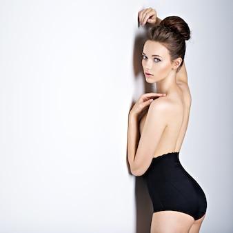 검은 란제리를 입고 긴 머리를 가진 아름답고 섹시한 여자의 스튜디오 샷