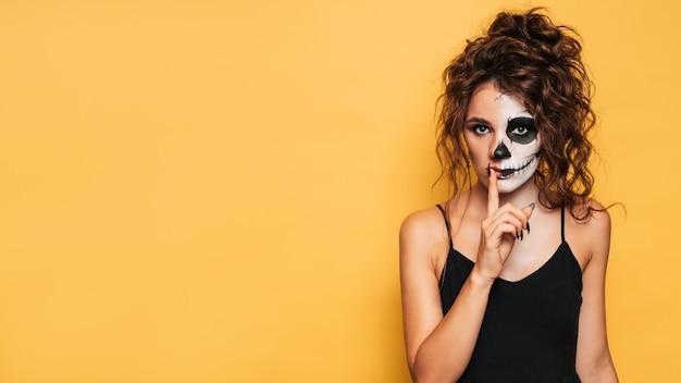 Студийный снимок девушки в костюме злых духов на костюмированной вечеринке на хэллоуин. место для вашего текста для товаров, рекламы. искусство хэллоуина.