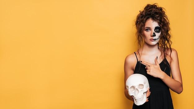 Студийный снимок девушки в костюме злых духов на костюмированной вечеринке на хэллоуин с черепом в руках, указывающей на пустое место для товаров, рекламы. искусство хэллоуина.