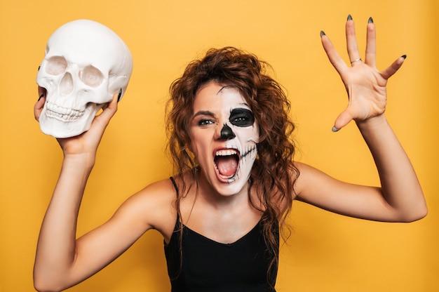 Студийный снимок девушки в костюме злых духов на костюмированной вечеринке на хэллоуин с черепом в руках. искусство хэллоуина.