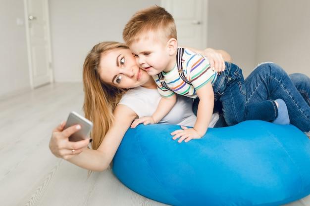 スマートフォンで彼女の子供を保持し、selfieを取る母のスタジオ撮影