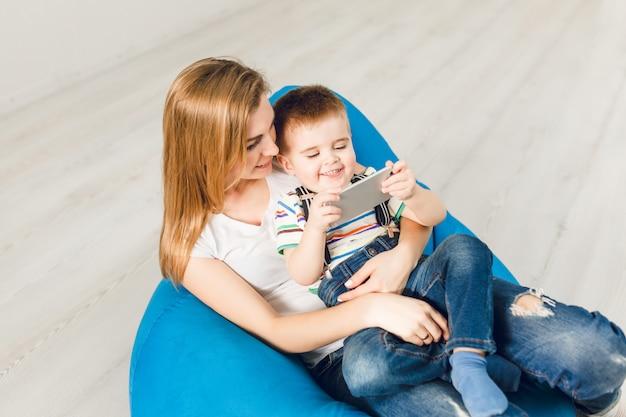 腕の中で彼女の子供を持つお母さんのスタジオ撮影。少年はスマートフォンで遊んで笑顔
