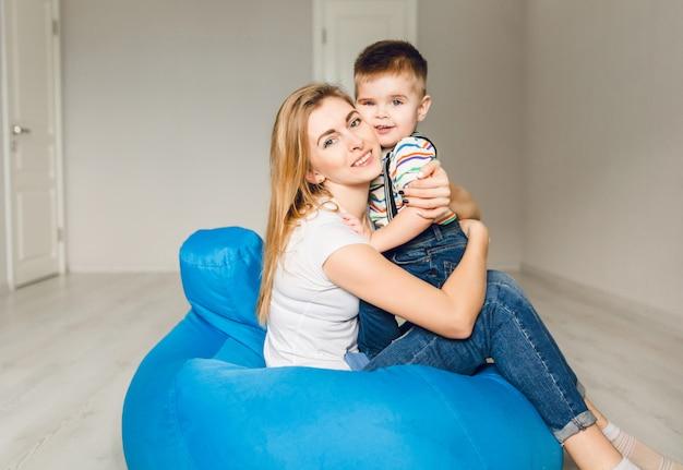 彼女の子供を持つお母さんのスタジオ撮影。ママは男の子を抱擁します。