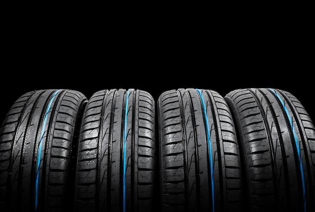 검은 배경에 여름 자동차 타이어 세트의 스튜디오 샷. 타이어 스택 배경. 자동차 타이어