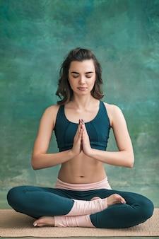 Съемка студии молодой подходящей женщины делая тренировки йоги на зеленом пространстве