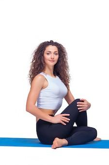 Съемка студии молодой подходящей женщины делая тренировки йоги.