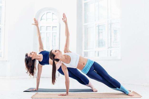Студия выстрел из молодых подходят женщины делают упражнения йоги