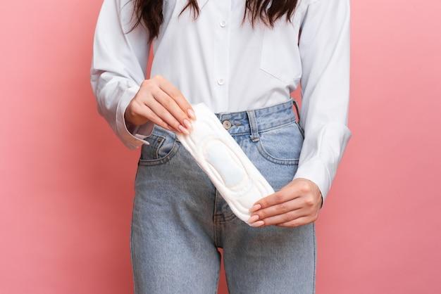 彼女の手に月経の詰め物を持った少女のスタジオショット。女性の衛生の概念。