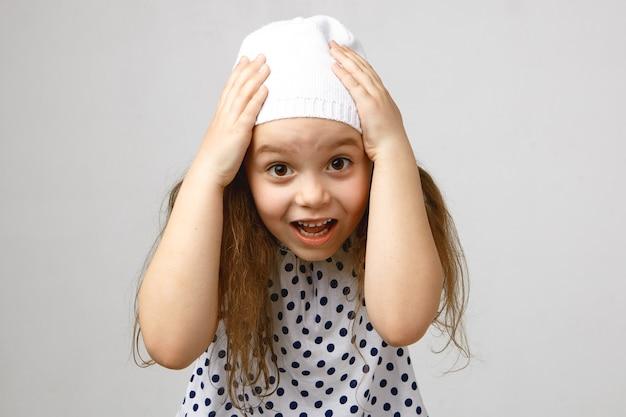 Студийный снимок очаровательной милой дошкольницы, выражающей шок и изумление