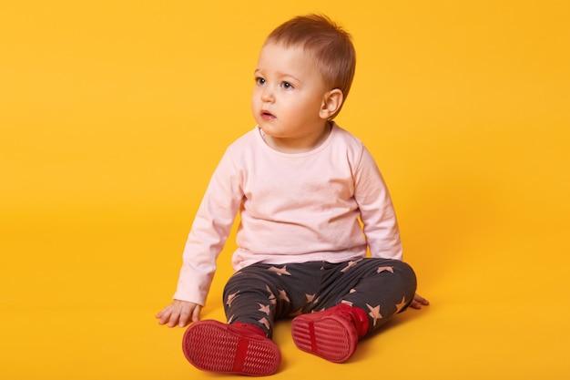 바닥에 앉아 사랑스러운 작은 여자 아기의 스튜디오 샷