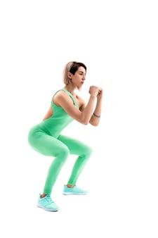 Студийный снимок спортивной женщины, делающей приседания, изолированные