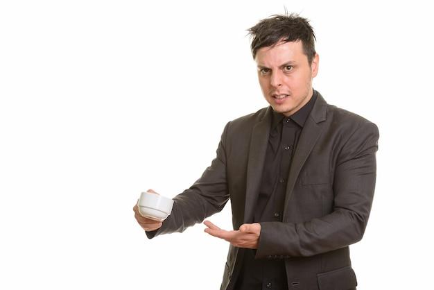 Студия выстрел сердитого кавказского бизнесмена, держащего чашку кофе