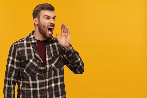 격자 무늬 셔츠에 화가 미친 수염 난 남자의 스튜디오 샷은 공격적으로 보이고 노란색 벽 위에 고립 된 측면으로 크게 비명을 지르는 것처럼 보입니다.