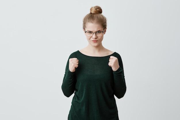 안경을 쓰고 찡그림, 분노와 광기를 표현 화가 자극 된 화가 금발의 젊은 여자의 스튜디오 샷. 걱정하고 긴장을 풀고 주먹을 떨리는 걱정되는 소녀