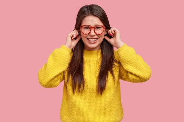 성가신 여자의 스튜디오 샷은 손가락으로 귀를 막고 부정성을 표현하고 이빨을 움켜 쥐고 캐주얼 한 노란색 옷을 입습니다.