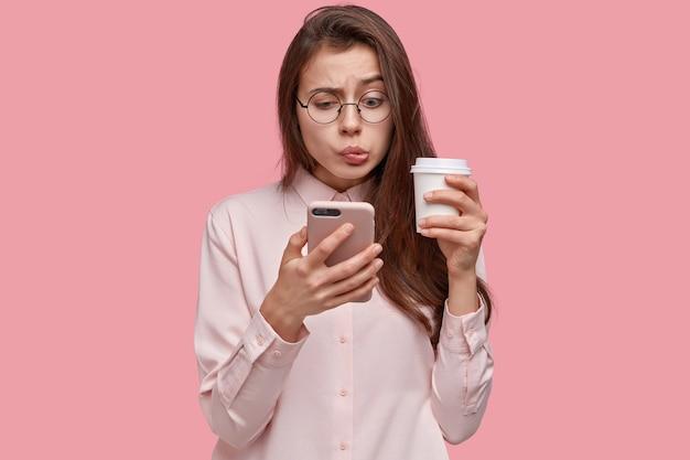 気になる困惑したかわいい女性のスタジオショットは元カレからのメッセージを読み、奇妙な情報を読みます